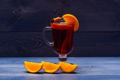 Mulled wine with orange juice. Drink and cocktail concept. Glass with mulled wine near juicy orange fruit on dark blue royalty free stock images