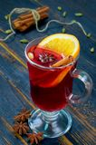 Mulled wine with orange slice and winter spices - cinnamon, cardamom and anise stars on the black wooden background. Close up view royalty free stock image
