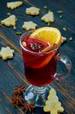 Mulled wine with orange slice and winter spices - cinnamon, cardamom and anise stars on the black wooden background. Decorated with Christmas cookies. Close up stock photos