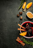 Mulled wine with orange slices on chalkboard - winter warming drink. Hot mulled wine with orange slices, anise and cinnamon sticks on black chalkboard from above stock image