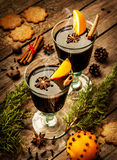 Mulled wine with orange slices on wood - winter warming drink. Hot mulled wine in a glass with orange slices, anise and cinnamon sticks on vintage wood table Stock Images