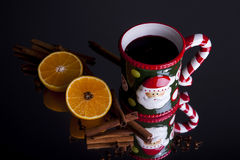 Mulled wine oranges and cinnamon sticks. Mulled wine in santa cup with oranges and cinnamon sticks shot at an angle on a grey background angle Royalty Free Stock Images
