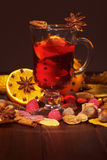 Mulled wine, oranges with cloves, nuts, raspberries, sweets on brown . Stock Photos