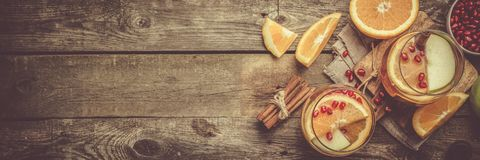 Mulled wine with oranges, pomegranate. Rustic background Stock Photos
