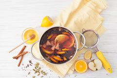 Mulled wine in the pan with ingredients on a white table Stock Photo