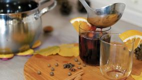 Mulled wine poured into a wineglass. Cooking traditional drink for Christmas. Mulled wine preparations. Close up stock video