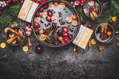 Mulled wine or punch in cooking pot and mugs with ingredients on dark rustic vintage background royalty free stock images