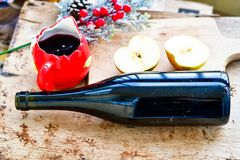 Mulled wine recipe ingredients. On  wooden background  - christmas or winter warming drink. Bottle and cup of  red wine, apple, orange  and mistletoe Royalty Free Stock Photo