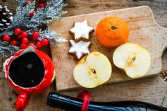 Mulled wine recipe ingredients. On  wooden background  - christmas or winter warming drink. Bottle and cup of  red wine, apple, orange  and mistletoe Stock Images