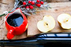 Mulled wine recipe ingredients. On  wooden background  - christmas or winter warming drink. Bottle and cup of  red wine, apple and mistletoe Royalty Free Stock Photos