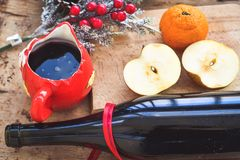 Mulled wine recipe ingredients. On  wooden background  - christmas or winter warming drink. Bottle and cup of  red wine, apple, orange  and mistletoe Royalty Free Stock Photography