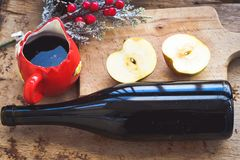 Mulled wine recipe ingredients. On  wooden background  - christmas or winter warming drink. Bottle and cup of  red wine, apple and mistletoe Stock Image