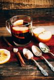 Mulled wine in rustic mug with spices and ingredients on wooden background. Top view, flat lay. Retro toned photo. Copy space for Royalty Free Stock Photo