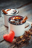 Mulled wine in rustic mugs with spices and red heart Stock Image