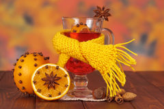 Mulled wine, scarf, oranges and nuts on background autumn leaves. Royalty Free Stock Photos