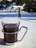 Mulled wine on ski piste. Warm mulled wine on the white table with the skiers going downhill on a sunny day Stock Photos