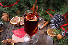 Mulled wine, sliced dried orange, cinnamon sticks, anise stars and candle with pine brunch Royalty Free Stock Image
