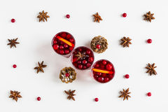 Mulled wine in small glasses with cranberries, anise and oranges. White background, top view Stock Photos
