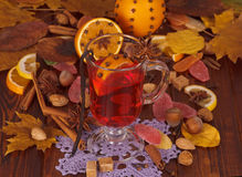 Mulled wine spices and fruit, nuts, candy on autumn leaves. Royalty Free Stock Photos