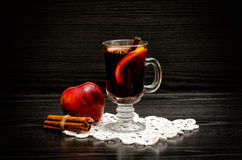 Mulled wine with spices on a lace napkin, apple and cinnamon sticks. Black wood background Stock Photo