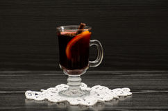 Mulled wine with spices on a lace napkin. Black wood background Royalty Free Stock Photography