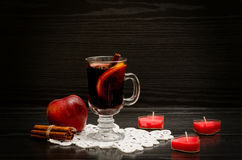 Mulled wine with spices on a lace napkin. Candles in the shape of a heart, cinnamon sticks and apple. Stock Photo