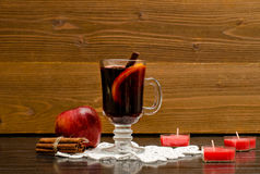 Mulled wine with spices on a lace napkin. Candles in the shape of a heart, cinnamon sticks and apple. Stock Image