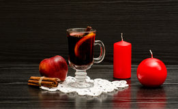 Mulled wine with spices on a lace napkin. Red candles, cinnamon sticks and apple. Black wood background Stock Images