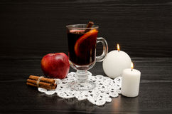 Mulled wine with spices on a lace napkin. White candles, cinnamon sticks and apple. Black wood background Royalty Free Stock Images