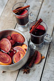 Mulled wine and spices on wooden background. Stock Photography