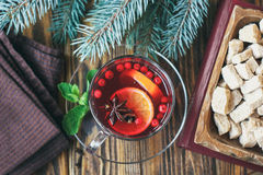 Mulled wine with spices on wooden background. Top view. Hot red mulled wine in transparent cup on wooden background decorated with christmas spices, orange slice Royalty Free Stock Image