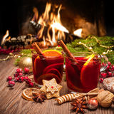 Mulled wine. Two glasses of mulled wine with christmas decoration at romantic fireplace royalty free stock images