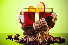 Mulled wine in two glasses and scarf on green Royalty Free Stock Image