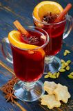 Mulled wine with various winter spices - cinnamon and anise stars on the black wooden background decorated with Christmas cookies. Close up view royalty free stock photos
