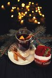 Mulled wine on white plate on black wooden table, cinnamon sticks and orange, christmas ball royalty free stock photos