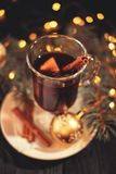 Mulled wine on white plate on black wooden table, cinnamon sticks christmas ball, lights royalty free stock photography