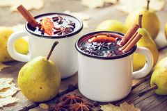 Mulled wine in white rustic mugs with spices and pear Royalty Free Stock Photography