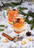 Mulled wine from white wine. On a snow-covered background with fir-tree branches Royalty Free Stock Photo