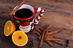 Mulled wine on wooden background angled. Mulled wine with an orange and cloves and cinnamon sticks shot from above at an angle on a brown wooden background Stock Images