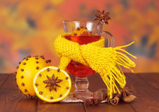 Mulled wine wrapped in scarf, oranges, hazelnuts on autumn leaves. Stock Images