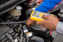 Multímetro de Checking Battery With del mecánico Foto de archivo libre de regalías