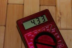 Multímetro de medição digital vermelho no assoalho de madeira Mostra 4 33V ou bateria inteiramente carregada Inclui o voltímetro, fotos de stock