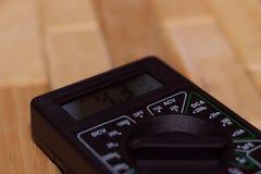 Multímetro de medición de Digitaces en piso de madera Muestra 4 33V o batería completamente cargada Incluye el voltímetro, amperm imagen de archivo