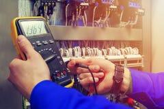 Multímetro nas mãos do close-up do eletricista contra o fundo de fios bondes e de relés foto de stock