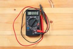 Multímetro y cableado de Digitaces en la tabla de madera herramientas del técnico para el trabajo con el circuito y eléctrico esp imagenes de archivo