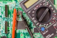 Multímetro y puntas de prueba de Digitaces en un primer verde de la placa de circuito Imagen de archivo libre de regalías