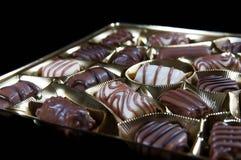 Multe confeitos brancos marrons sortidos do chocolate no pacote dourado Fotografia de Stock