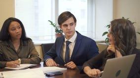 3 multi этнических коллеги обсуждая проект в офисе сток-видео