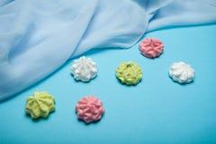 Multi покрасил форму сладкой меренги традиционную изолированный на голубой предпосылке стоковые изображения