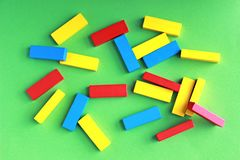 Multi покрашенные блоки игрушки лежа на зеленой предпосылке стоковое изображение